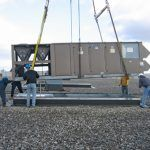 The technicians put one of the five 40-ton rooftop HVAC units in place on the newly reinforced roof